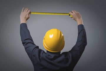 engineer in a helmet uses a tape measure