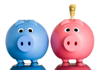 Two piggy banks with money in one.