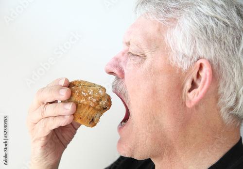 man eats blueberry muffin