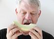 older man eating melon slice