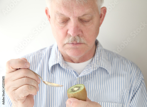 senior prepares to eat kiwifruit