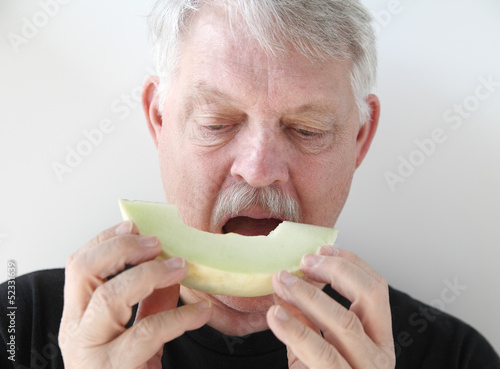 older man eating melon slice