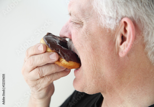 man takes bite of chocolate glazed doughnut