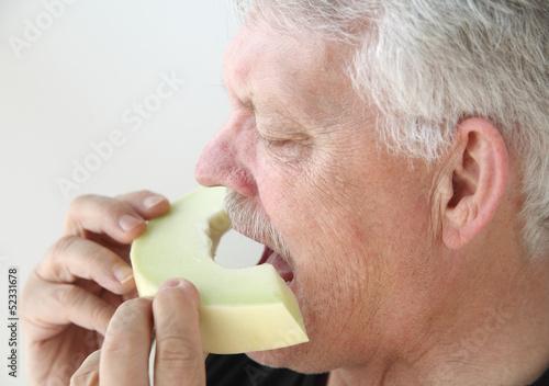 senior man eats fresh honeydew melon