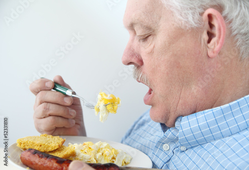 senior eats breakfast eggs
