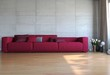 Rotes Sofa vor Betonwand