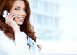 Beautiful business woman talking on cell phone while looking at