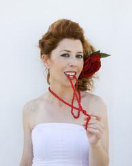 Mujer mordiendo su collar de perlas rojo.