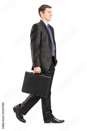 Full length portrait of a businessman walking and holding a brie