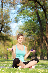 Young female exercising with dumbbells in park