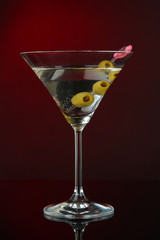 Martini glass with olives on dark red background