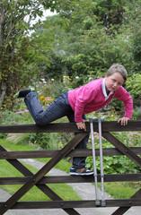 Young boy with walking sticks climbing gate