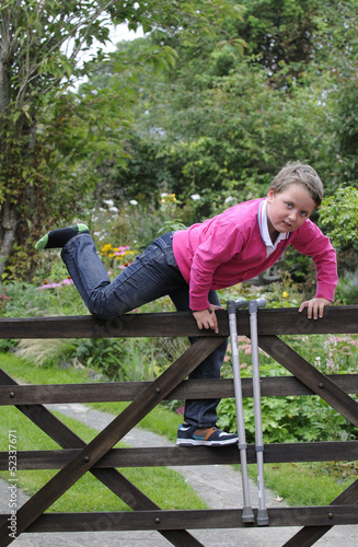 Young boy with walking sticks climbing gate
