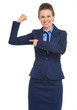 Smiling business woman pointing on biceps