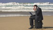 Angry businessman with cellphone and laptop on the beach