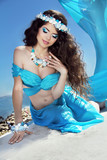 Long Healthy Hair. Beautiful brunette woman in blue silk luxury