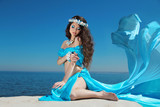 Beautiful woman model in Blowing Dress Flying resting over blue