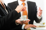 businesspersons in business office drinking coffee