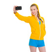 Happy teenager girl taking photo with cell phone