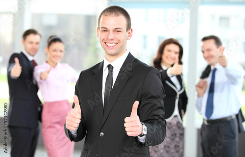 Cheerful business man with team giving you thumbs up