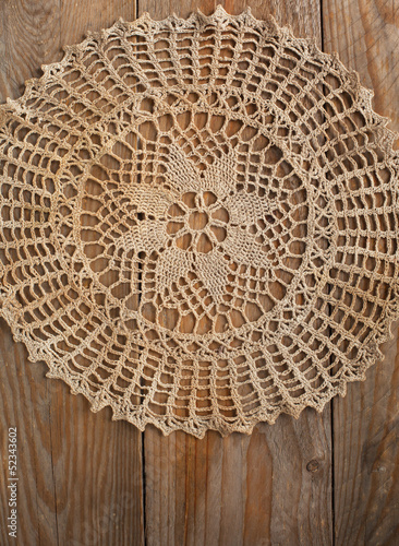 Old handmade crochet doily over wooden background