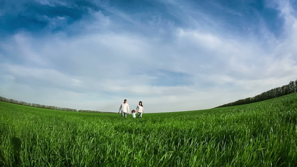 Happy family running in green field. Slow motion