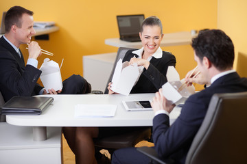 Business people laughing during lunch break in the office