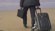 Businessman with suitcase walking on beach, super slow motion