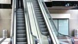 Confident businessman walking off an escalator