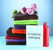 Pile of colorful towels, wash powder and bottle of conditioner