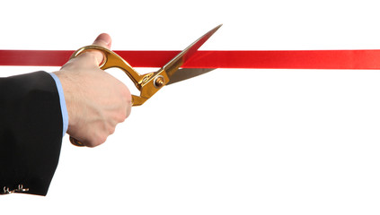 Man's hand cutting red ribbon with pair of scissors isolated