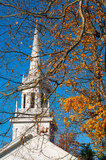 Old-fashioned church spire against a blue autumn sky
