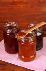 Tasty jam in banks on wooden background