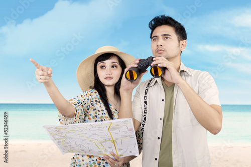 Asian couple using binoculars at beach
