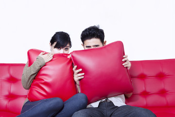 Asian couple hide behind pillow on red sofa - isolated