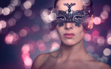 Beautiful young woman in black mysterious venetian mask.