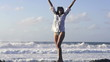 Happy, excited woman standing by the sea, super slow motion