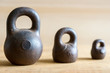 Three small calibration weights on wooden background. Small DOF