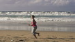 Young woman jogging on beautiful beach in the morning