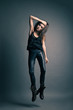 Fashion model wearing leather pants jump on grey