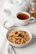 Muesli granola with raisin and yogourt in white bowl