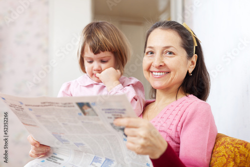 Mature woman and  girl reads newspaper