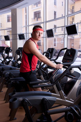 Attractive man in red sportswear doing exercises on bike at gym
