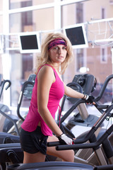 Beautiful blonde woman doing exercise on bike in gym