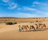 Two cameleers with camels in dunes of Thar deser