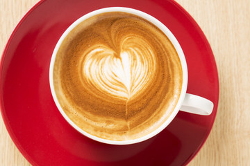 Zoomed cup of coffee with foam heart