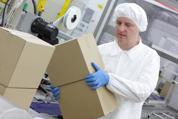manual worker at production line dealing with boxes