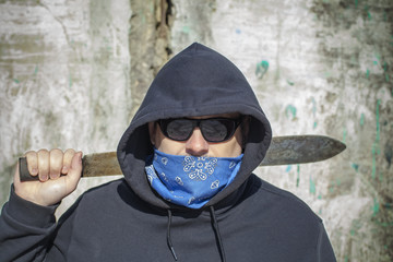 Man with a machete on a old wall background