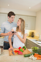 Couple cooking and clinking wine glasses