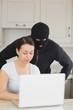 Burglar looking at the laptop behind  woman